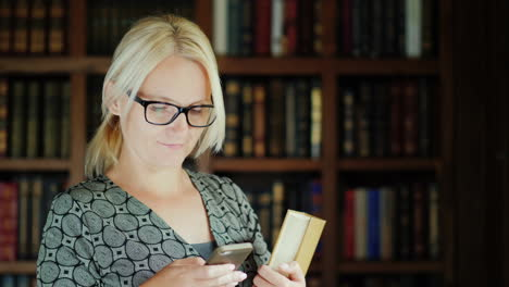 Woman-Holding-Book-Using-Smartphone