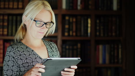 Woman-in-Glasses-Using-Tablet-by-Bookshelf