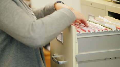 Woman-Removes-File-From-Filing-Cabinet