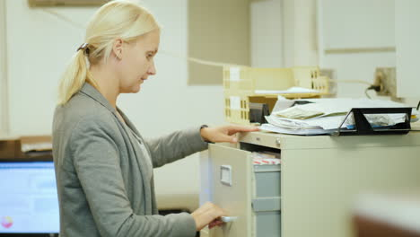 Woman-Removes-Document-From-Filing-Cabinet