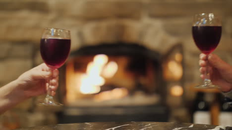 Clinking-Wine-Glasses-by-Burning-Fireplace