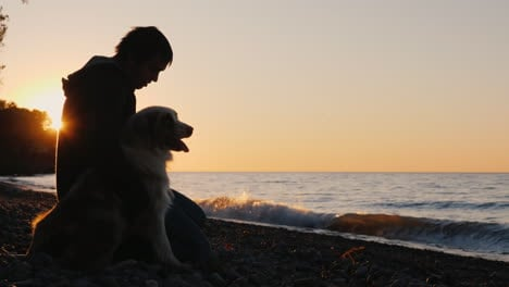 Man-and-Dog-bu-a-Lake-at-Sunset