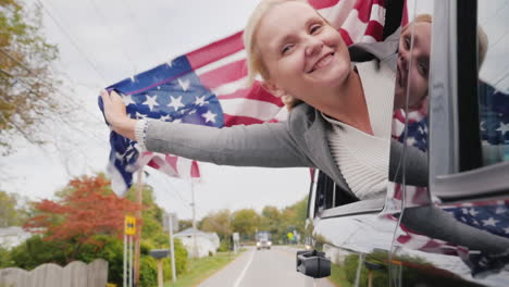 Woman-Leans-Out-of-Car-With-USA-Flag