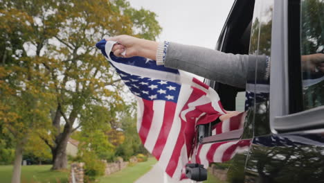 Hands-Hold-American-Flag-Out-of-Car-Window