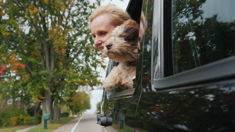Woman-and-Dog-Lean-Out-of-Car-Window