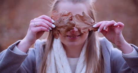 Smiling-Woman-Hiding-Eyes-With-Leaves-In-Autumn-2