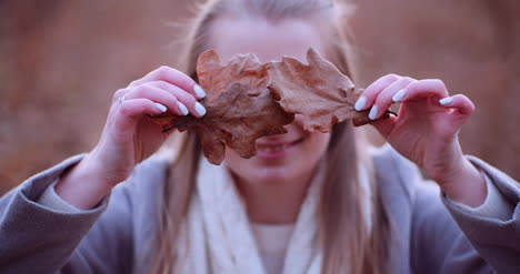 Smiling-Woman-Hiding-Eyes-With-Leaves-In-Autumn-3