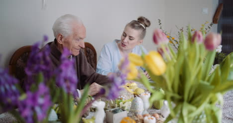 Happy-Easter-Senior-Man-And-Young-Woman-Conversating-During-Easter-Holidays