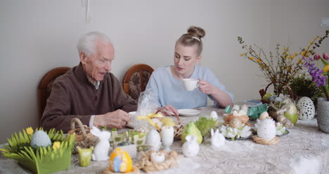 Happy-Easter-Senior-Man-And-Young-Woman-Drinking-Tea-During-Easter-Holidays