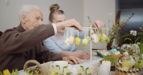 Senior-Man-And-Granddaughter-Decorating-Table-With-Easter-Eggs-And-Easter-Decorations-