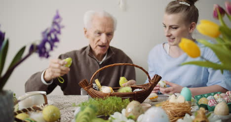 Senior-Man-And-Young-Woman-Putting-Easter-Eggs-Into-Basket-