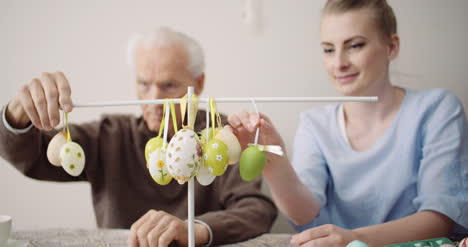 Senior-Man-And-Granddaughter-Decorating-Table-With-Easter-Eggs-And-Easter-Decorations-4