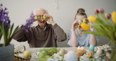 Happy-Easter-Cheerful-Grandfather-And-Granddaughter-Play-With-Easter-Eggs-On-Easter