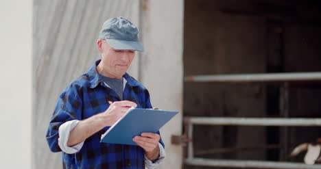 Farmer-Gesturing-While-Writing-On-Clipboard-Against-Barn-7