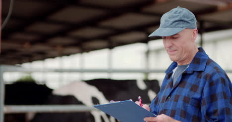 Farmer-Gesturing-While-Writing-On-Clipboard-Against-Barn-8