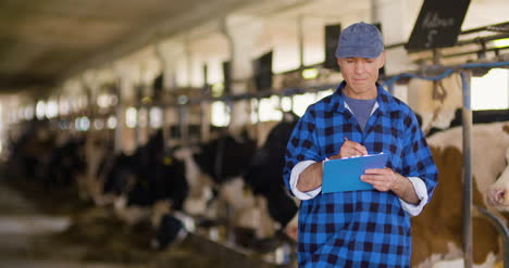 Farmer-Gesturing-While-Writing-On-Clipboard-Against-Barn-9