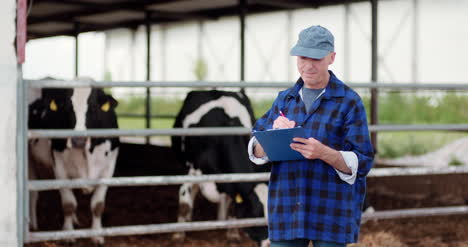 Farmer-Analyzing-And-Writing-On-Clipboard-Against-Cowshed-9