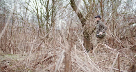 Man-Holding-Fishing-Rod-Walking-Amidst-Bare-Trees-1