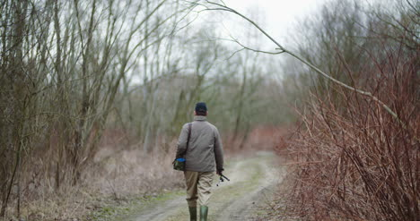 Man-Holding-Fishing-Rod-Walking-Amidst-Bare-Trees-5