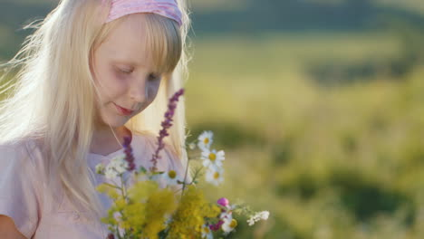 Cute-Little-Girl-Enjoying-Nature-Looking-At-Bouquet-Of-Wildflowers