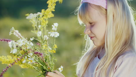 Cute-Little-Girl-Collects-Composition-From-Wild-Flowers-On-A-Background-Of-Green-Landscape