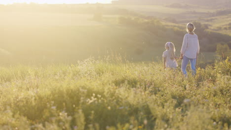 Young-Cute-Woman-Walking-With-Little-Daughter-Over-The-Field-Looking-At-Green-Meadow-On-Sunset-Backg