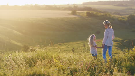 A-Little-Cool-Girl-With-Blond-Hair-Shows-Mom-A-Beautiful-Sunset-Over-Green-Fields-Back-View