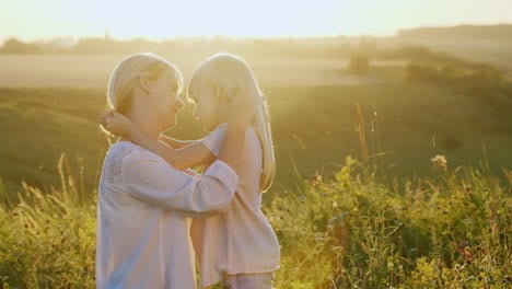 A-Young-Mother-Calming-Her-Child-Stroking-Her-Blond-Hair-Outdoors