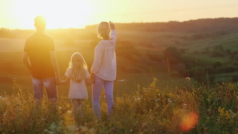Young-Family-Of-Three-People-Enjoying-The-Sunset-On-A-Cliff