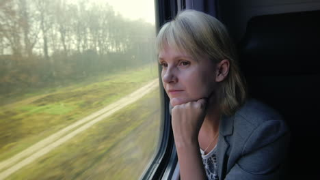 Young-Woman-Travels-By-Train-Looks-Out-The-Window-At-Beautiful-Scenery-Dreams-Slow-Motoin-Video