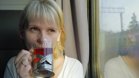 A-Woman-Is-Drinking-Tea-On-The-Train-Traveling-With-Comfort-4k-Video