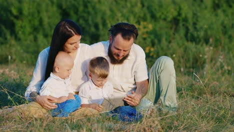 Two-Small-Brothers-With-Their-Parents-Play-On-A-Tablet-Among-The-Flowering-Meadow