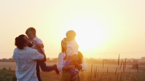 Young-Family-With-Two-Children-Playing-On-Nature-On-The-Sunset