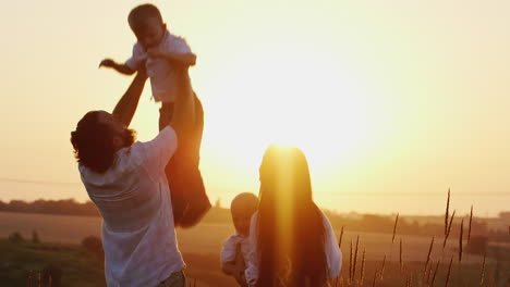 Young-Man-And-Woman-Playing-With-Young-Children-Tosses-Them-In-The-Air-Against-The-Sunset-Background