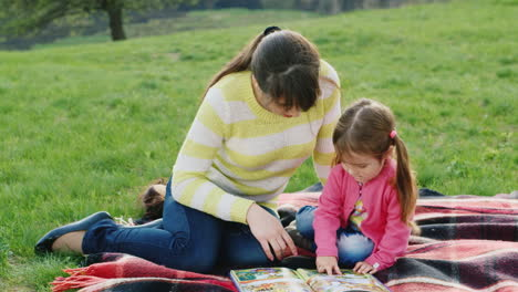 A-Young-Mother-Reads-Together-With-Her-Daughter-An-Interesting-Book-On-Nature