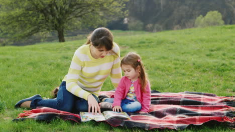 A-Young-Woman-Sits-On-The-Green-Grass-And-Teaches-Her-Daughter-To-Read-A-Book-In-The-Nature