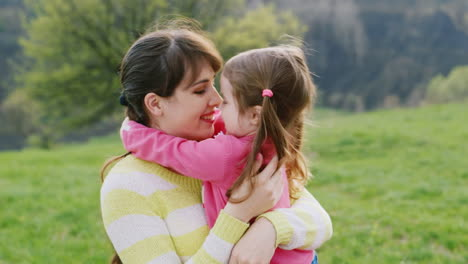 Little-Girl-Hugging-With-Her-Young-Mother-In-The-Spring-Garden