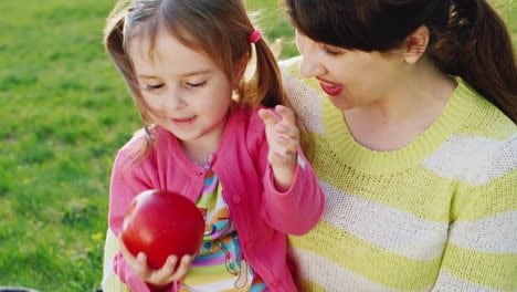 A-Little-Girl-Is-Sitting-In-Her-Mother-s-Arms-And-Playing-With-A-Red-Ripe-Apple