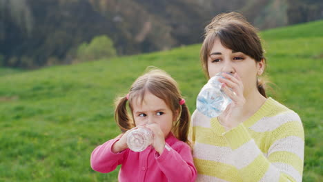 A-Young-Pretty-Woman-Drinks-Clean-Water-From-A-Plastic-Bottle-Along-With-Her-Little-Daughter