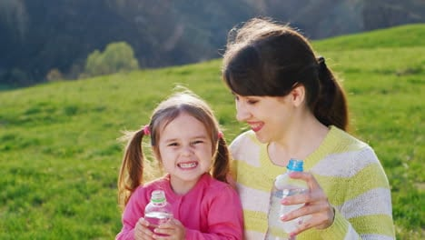 A-Funny-Girl-Of-3-4-Years-With-Her-Lovely-Mother-Drinks-Water-The-Sun-s-Rays-Illuminate-Them-On-A-Gr