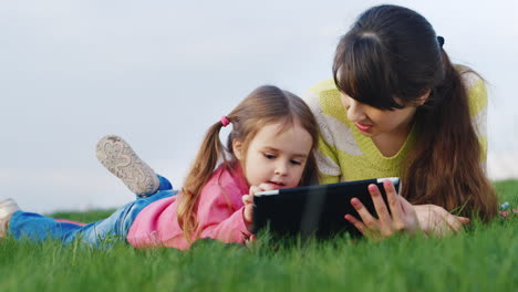 Funny-Little-Girl-Lie-On-Green-Juicy-Grass-And-Play-On-Tablet