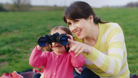 A-Young-Mother-Shows-Her-Hand-To-The-Distance-And-Her-Little-Daughter-Looks-Carefully-Through-Binocu