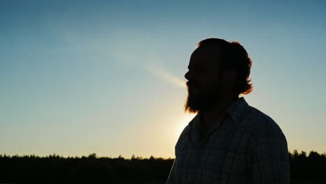 Silhouette-Of-A-Bearded-Man-Who-Smokes-At-Sunset