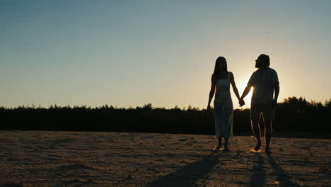 Romantic-Young-Couple-Walking-At-Sunset