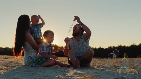 Young-Parents-And-Two-Sons-Of-The-Family-Playing-With-Soap-Bubbles-At-Sunset