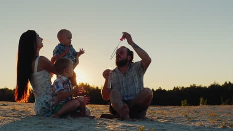 Young-Family-Having-Fun-With-Two-Kids---Blow-Bubbles-At-Sunset