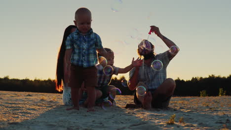 Parents-Play-With-Two-Boys-At-Sunset---Blow-Bubbles