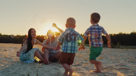 Young-Family-Having-Fun-With-Kids---Blow-Bubbles-At-Sunset