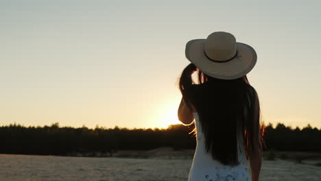 Young-Woman-With-Long-Hair-In-A-Hat-Go-Towards-The-Setting-Sun-Rear-View