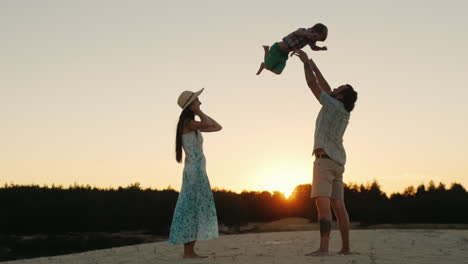 Young-Happy-Family-Playing-With-His-Son-At-Sunset-Father-Tossing-Baby
